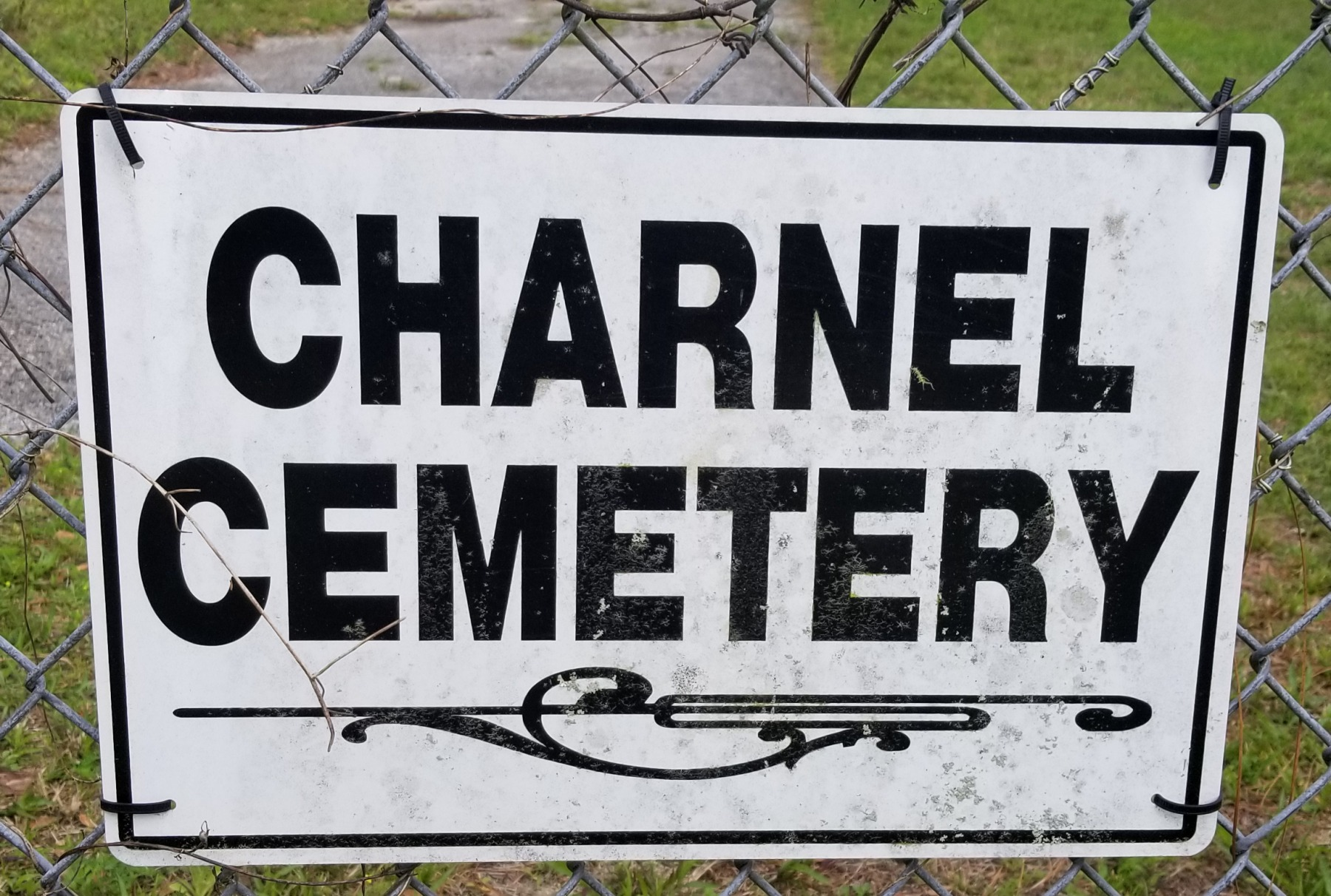 Charnel Cemetery sign located on fence gate